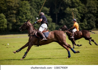 The Polo Player hits the ball towards the goal.