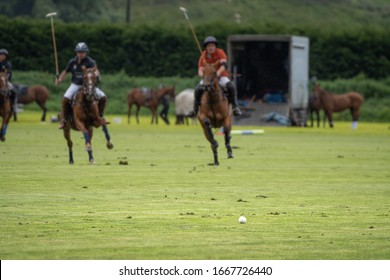 Polo players on the field. Ball on the foreground and player on their horses on the backgrounds