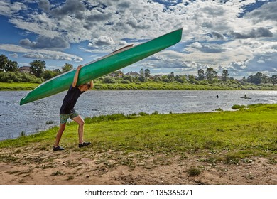 Polotsk, Belarus - July 6, 2018: One teen boy carrying their canoes on their shoulders after kayak slalom.