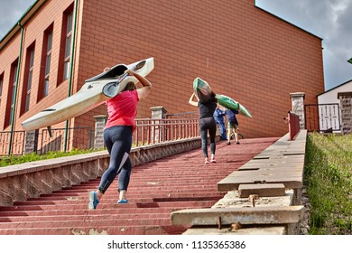 Polotsk, Belarus - July 6, 2018: Teenagers come back to building of sports section after rowing training, they rise up an abrupt ladder, bearing canoe on their shoulders.