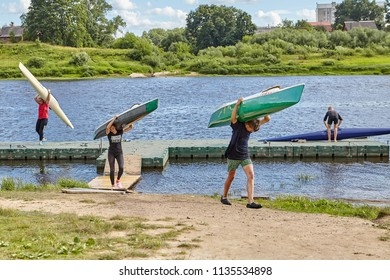 Polotsk, Belarus - July 6, 2018: Young fans of sports rowing carry away kayaks from Western Dvina River, having shipped them on shoulders.