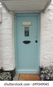 Polperro, Cornwall - a pale blue front door in a white walled house