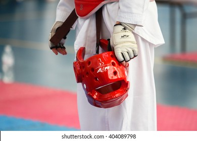"Poltava, April 10, 2016 - Red protective helmet in the hands of the athlete during the tournament taekwondo ""Olympic star"" in the sports complex ""Dynamo"" in Poltava, Ukraine."