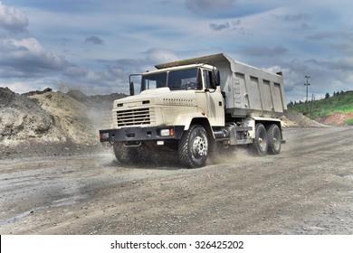 Poltava Region, Ukraine - June 26, 2010: Dump truck driving along the muddy road on the iron ore opencast