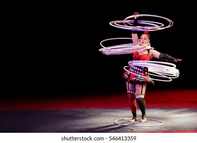 POLTAVA, UKRAINE - DECEMBER 19, 2016: Gymnast throws in air 30 hoops (Hula hoops)during the performance of circus show Kobzov