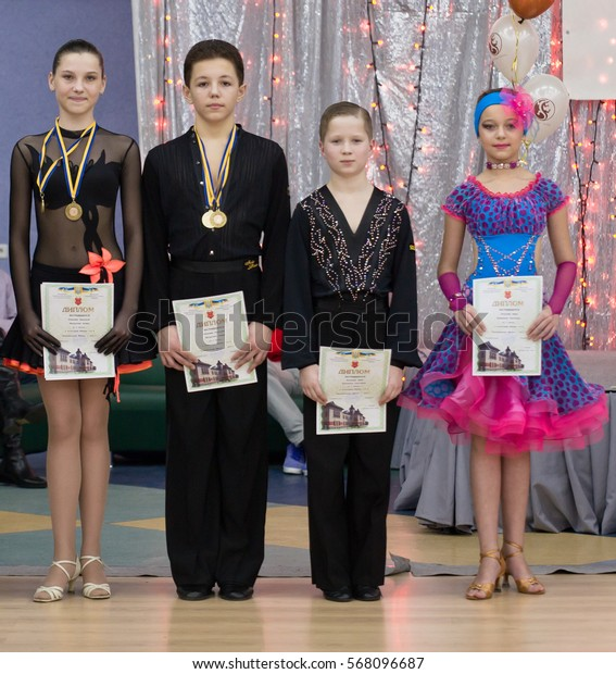 POLTAVA, UKRAINE - December 4, 2011: Unidentified young participants posing during the national ballroom dance tournament. A bit of grain in effect.
