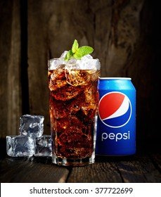 POLTAVA, UKRAINE, FEBRUARY 15, 2016  Can and glass of Pepsi-Cola with ice on wooden background. Pepsi is a carbonated soft drink sold in stores, restaurants, and vending machines throughout the world.