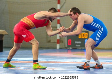 POLTAVA, UKRAINE -  FEBRUARY 8, 2018: Two male wrestlers struggling on the carpet during Ukrainian Championship among men and women under the age of 23 in Dynamo Sports Complex