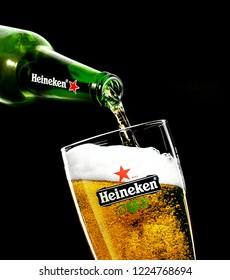 POLTAVA, UKRAINE - June 18, 2018:Heineken beer is pouring into a glass over black  background. Heineken is the flagship product of Heineken International