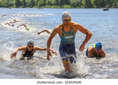 POLTAVA, UKRAINE – JUNE 3, 2017: Triathletes after swimming in a river runs ashore during nationwide competitions on triathlon «Triathlon Poltava Sprint 2017» in Poltava, Ukraine