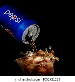 POLTAVA, UKRAINE - MARCH 22, 2018: Splash pepsi into a glass on a black background. Pepsi is a carbonated soft drink produced PepsiCo. Created in 1893
