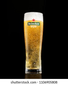 POLTAVA, UKRAINE - MARCH 22, 2018: A Glass of beer Heineken Lager on a black background.Heineken Lager Beer is a pale lager beer produced by the Dutch brewing company Heineken International