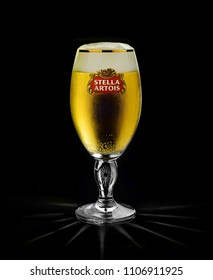 POLTAVA, UKRAINE - MARCH 22, 2018: Cold glass of Stella Artois beer on black background, prominent brand of Anheuser-Busch InBev, is a pilsner brewed in Leuven, Belgium, since 1926