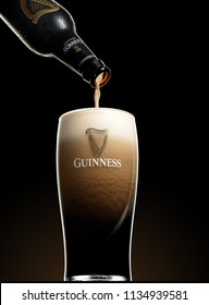 POLTAVA, UKRAINE - MARCH 22, 2018: Guinness beer is pouring into a glass. Guinness beer has been produced since 1759 in Dublin, Ireland.