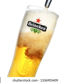 POLTAVA, UKRAINE - MARCH 22, 2018:Heineken beer is pouring into a glass over white background. Heineken is the flagship product of Heineken International