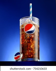 POLTAVA, UKRAINE, OCTOBER 17, 2017: glass of Pepsi-Cola with ice   on blue background.Pepsi is a carbonated soft drink sold in stores, restaurants, and vending machines throughout the world