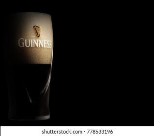 POLTAVA, UKRAINE - OCTOBER 4, 2017:Glass of Guinness original beer on black background. Guinness beer has been produced since 1759 in Dublin, Ireland.