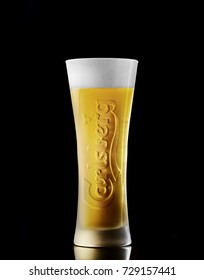 POLTAVA, UKRAINE - OCTOBER 6, 2017: Cold glass Of Carlsberg beer on black background. Danish brewing company founded in 1847.