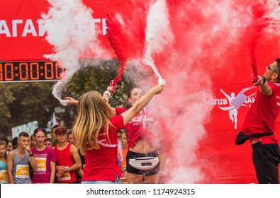 POLTAVA, UKRAINE - SEPTEMBER 2, 2018: Organizers throw in paint paint during the Poltava Nova Poshta semi-marathon at the Theater Square