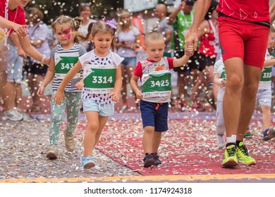 POLTAVA, UKRAINE - SEPTEMBER 2, 2018: Children run along the road during the Poltava Nova Poshta semi-marathon at the Theater Square