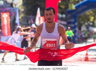 POLTAVA, UKRAINE - SEPTEMBER 2, 2018: Ukrainian runner Pavel Oliynyk finishes during the Poltava Nova Poshta semi-marathon at the Theater Square