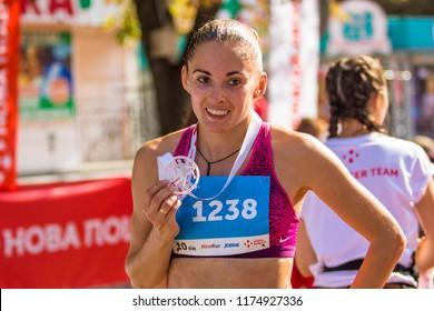 POLTAVA, UKRAINE - SEPTEMBER 2, 2018: Women are participants in the race with award-winning finishers during the Poltava Nova Poshta semi-marathon at the Theater Square