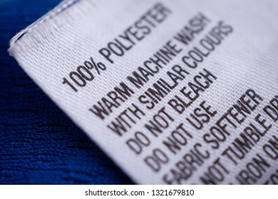 Polyester clothing label with laundry care instructions tag on blue shirt jersey