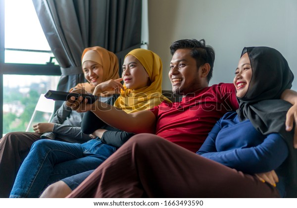 Polygamy concept husband with 3 wife at the sofa watching television