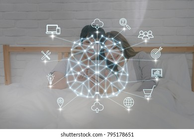 Polygonal brain shape of an artificial intelligence with various icon of smart city Internet of Things Technology over Happy Asian Lover on the bed in bedroom at home, AI and business IOT concept