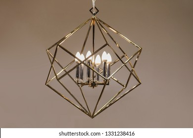 Polygonal chandelier, gold, brass, different shapes of a triangle, inside lamp there are candles. Fashion design chandeliers.