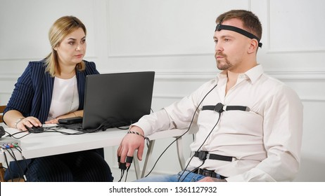 polygraph technician reads questions from a laptop. man connected to the lie detector circuit.