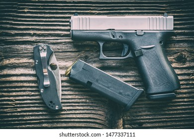 Polymer pistol and ammunition with folding knife on wooden background. EDC defence concept.