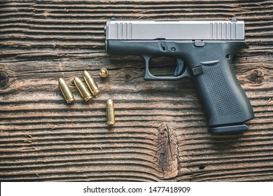 Polymer pistol and ammunition on wooden background. EDC defence concept.