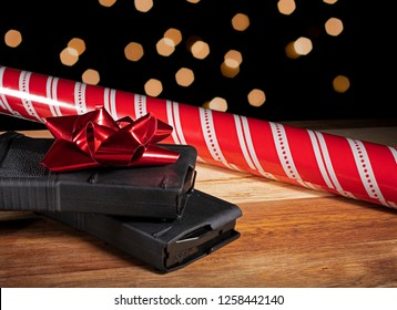 Polymer rifle magazines with Christmas wrapping paper and lights behind