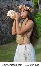 Polynesian Cook Islander  woman blowing conch shell in Rarotonga, Cook Islands. Real people Copy space