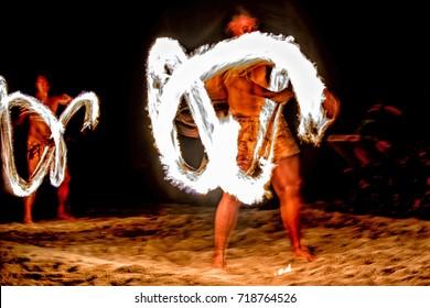 polynesian dancer using flame pole on black background