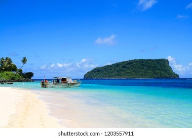 Polynesian fisherman boat dock on white golden sandy Lalomanu beach at tropical paradise in Pacific Ocean's Upolu Island, turquoise coral waters with view of Nu'utele island