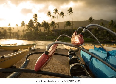 Polynesian outrigger canoe on the beach in the evening