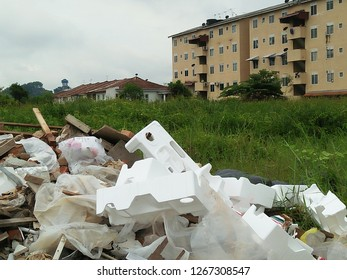 Polystyrene boxes  at a rubbish dump site behind a row of houses.