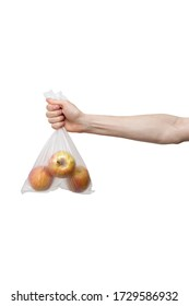 polythene bag held in hand isolated on white. man holding packet of yellow and red apples. delivery from shop to home. food supplies, donation, volunteer. product ingredients for dish, cooking meals