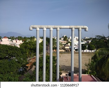 Polyvinyl chloride also known as PVC water pipes connected to overhead tank forming abstract of lines or pattern seen with metal valves for closing and opening the water flow.