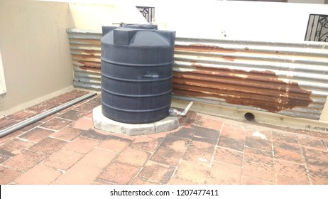 Polyvinyl chloride known as PVC water pipes connected to unidentified overhead tank forming abstract of lines or pattern seen with metal valves for closing and opening the water flow