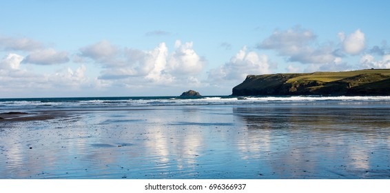 Polzeath beach, North Cornwall, UK in the early morning sun with clouds reflected in the wet sand