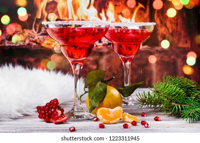 Pomegranage and tangerine martini on festive holiday background. Christmas celebration cocktails near burning fireplace. Copy space