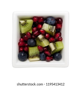 Pomegranate arils, blueberries and diced kiwifruit in a square bowl isolated on white background
