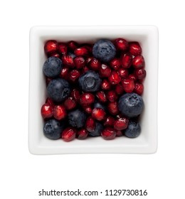 Pomegranate arils and blueberries in a square bowl isolated on white background