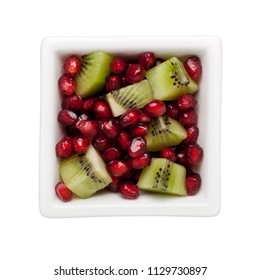Pomegranate arils and diced kiwifruit in a square bowl isolated on white background
