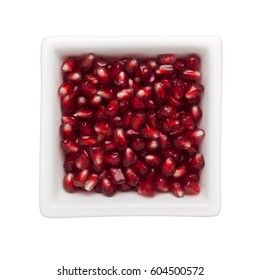 Pomegranate arils in a square bowl isolated on white background