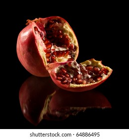 pomegranate, broken fruit isolated on black reflective surface