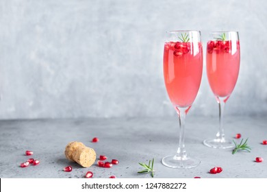 Pomegranate Champagne Mimosa Cocktail (Mocktail) with rosemary on concrete background, copy space. Mimosa Drink for Valentine Day or other holidays.